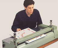 "The Adjutant Press is used to smooth out the combined glued print/board combination to insure that there are no air bubbles or wrinkles up to 1/8"" thick."